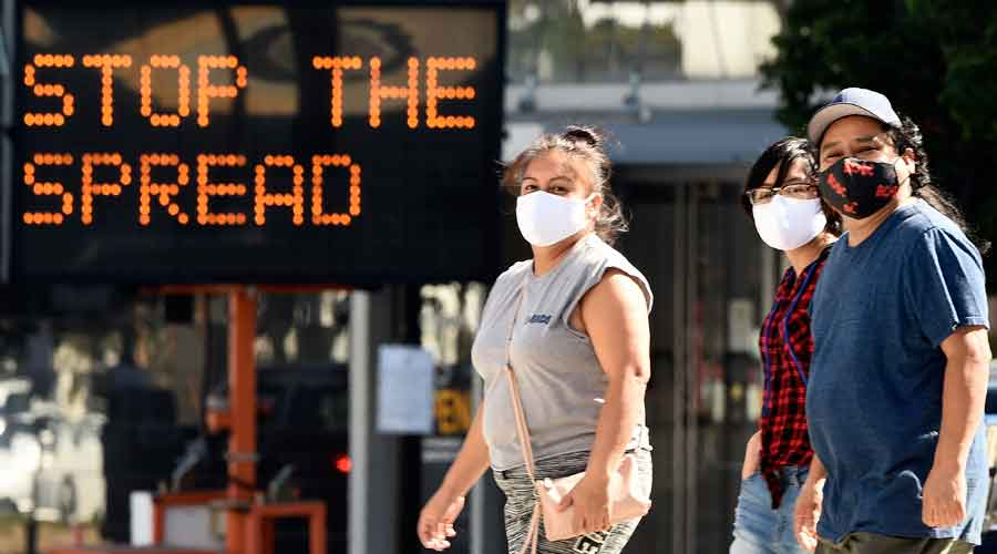 Pedestrians wear masks as they walk in front of a sign reminding the public to take steps to stop the spread of coronavirus in California