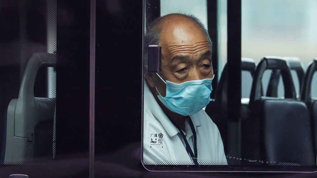 A man wearing a face mask to protect against the new coronavirus rides alone on a bus in Beijing, Tuesday, July 28, 2020.