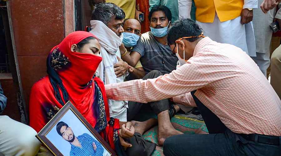 District Magistrate Brahma Deo Ram Tiwari consoles relatives of lab technician Sanjeet Yadav who are staging a dharna demanding CBI probe in his kidnapping and murder case in Kanpur on Saturday.