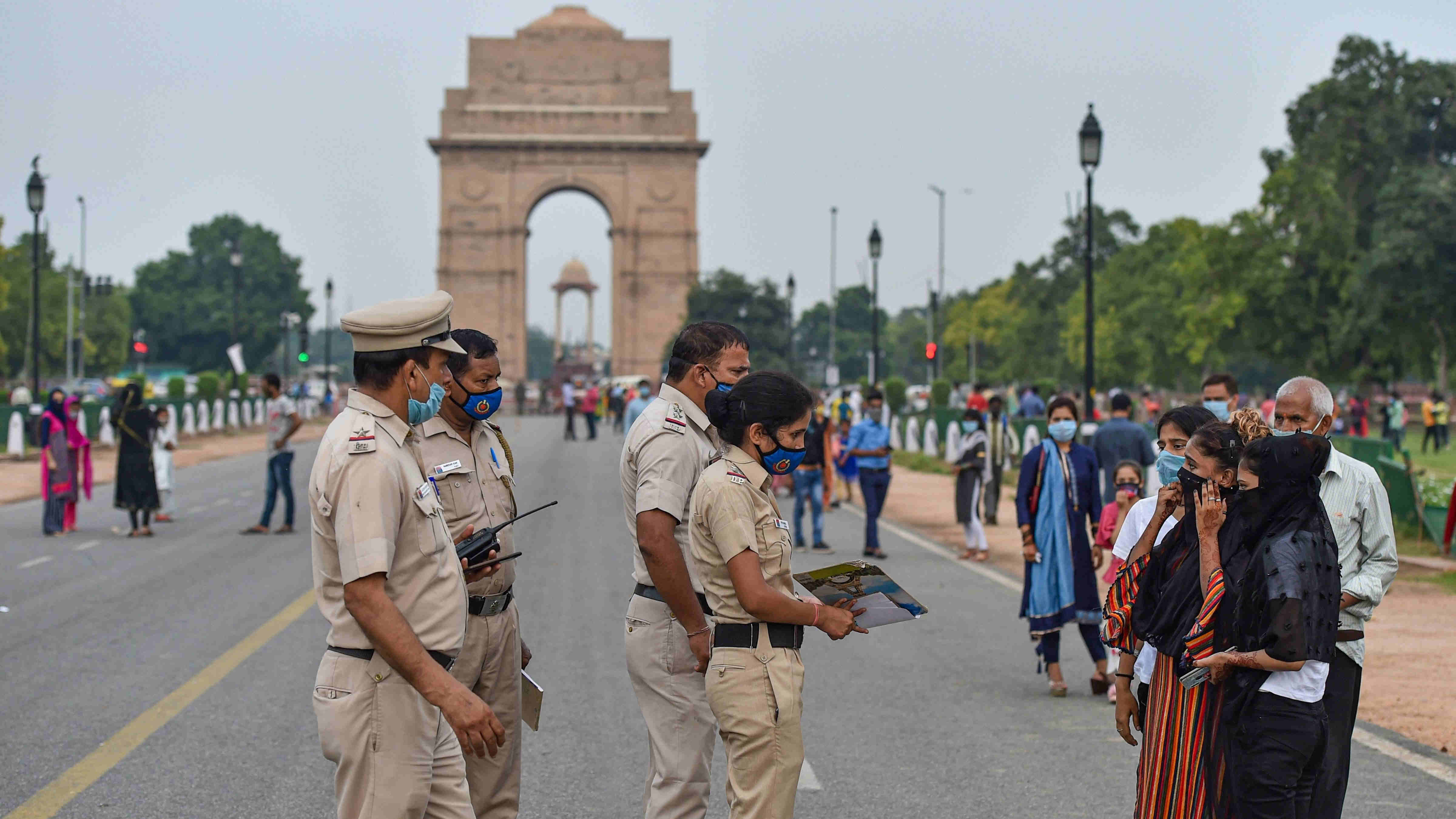 Policemen warn visitors of penalties for not wearing masks near India Gate during Unlock 3.0, in New Delhi, Saturday, Aug 1, 2020.