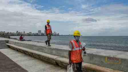 Workers walk along the Marine Drive in Mumbai, Friday, July 31, 2020.