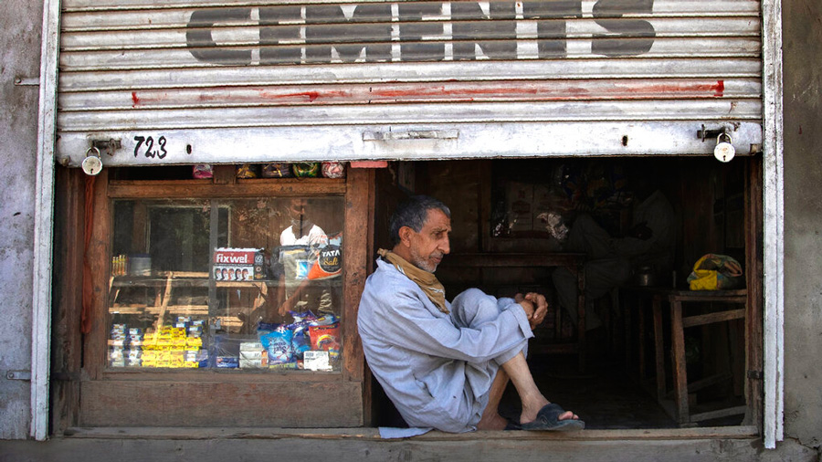 A Kashmiri shopkeeper sits at the entrance of his half closed shop during lockdown in Srinagar, Kashmir, July 27, 2020