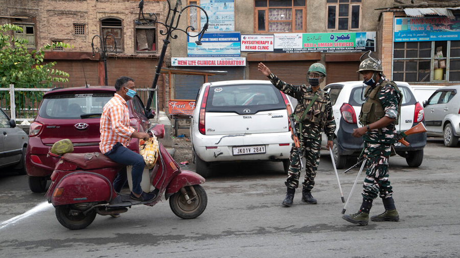 Indian paramilitary soldiers stop a Kashmiri man traveling to visit relatives for Eid during lockdown in Srinagar, Saturday, Aug. 1, 2020.