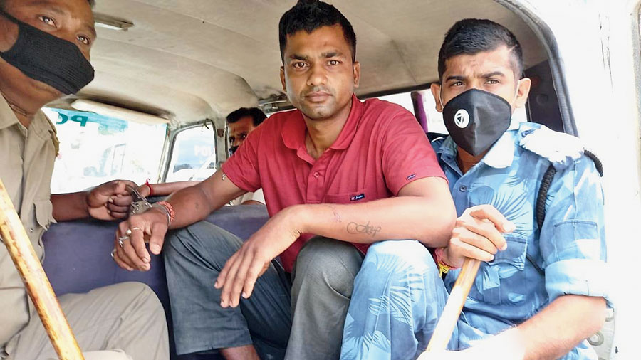 Uttam Sutradhar (centre) in a police vehicle in Raiganj on Wednesday