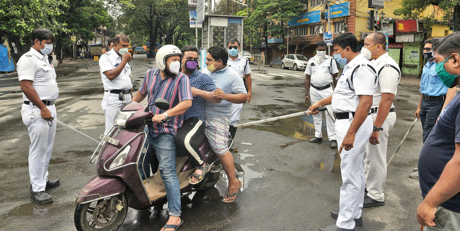 lockdown check: Police stop a scooter with three men, two of whom were not wearing helmets, on CIT Road during the lockdown around noon on Wednesday. When asked why they were out, the three said they were going to a hospital. Cops let two of them go, the third was made to return home.