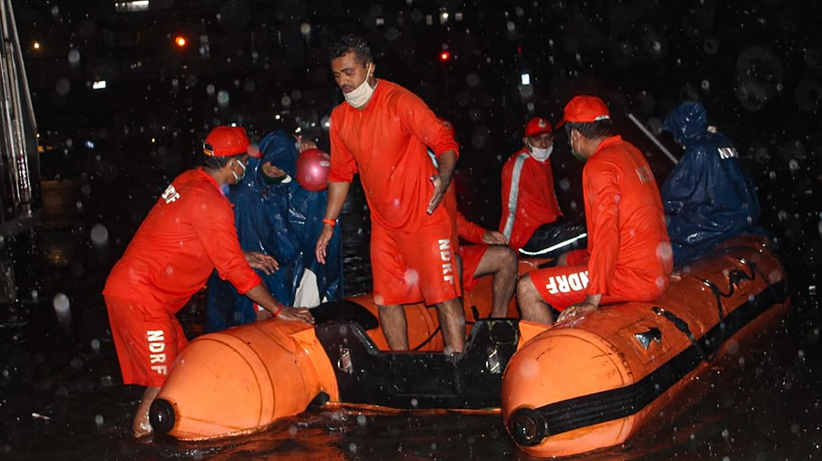 National Disaster Response Force (NDRF) personnel rescue passengers from a local train stranded between Masjid Bunder and Byculla stations on the Central line, during heavy rain in Mumbai on Wednesday