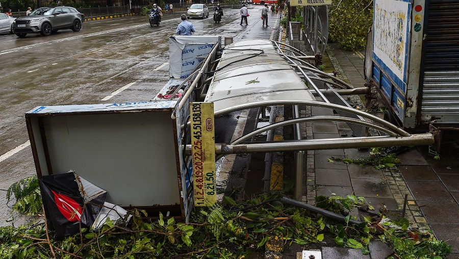People walk past a damaged bus stand that collapsed during heavy rain at Churchgate on Thursday