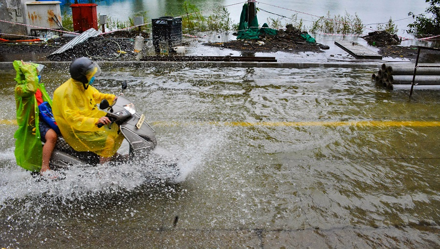 A motorist rides through a waterlogged road near the swollen Masunda Lake following incessant rains, in Thane on Thursday