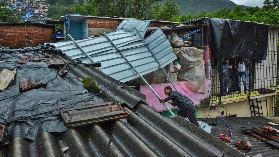 A man repairs the roof of his house damaged during heavy rains at Indira Nagar area of Thane on Thursday