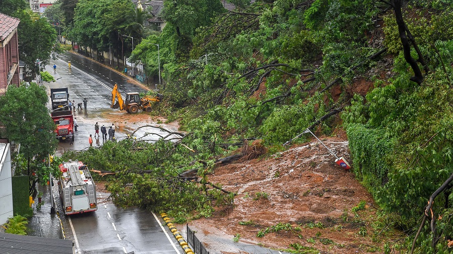 Municipal workers clear debris from Pedder road, after a landslide due to heavy rainfall on Thursday