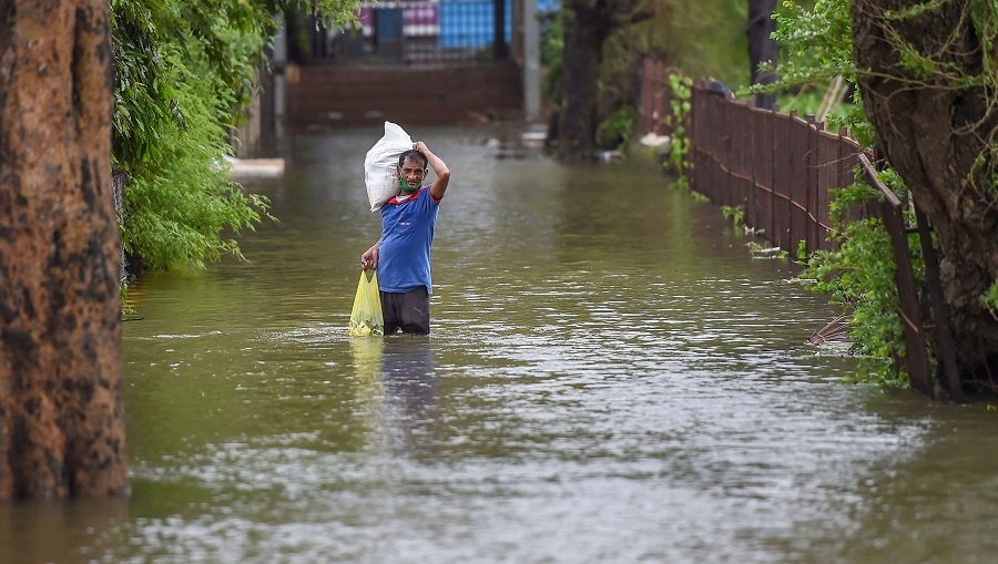 A man wades through a waterlogged area after heavy rainfall, at Grant Road in Mumbai on Thursday