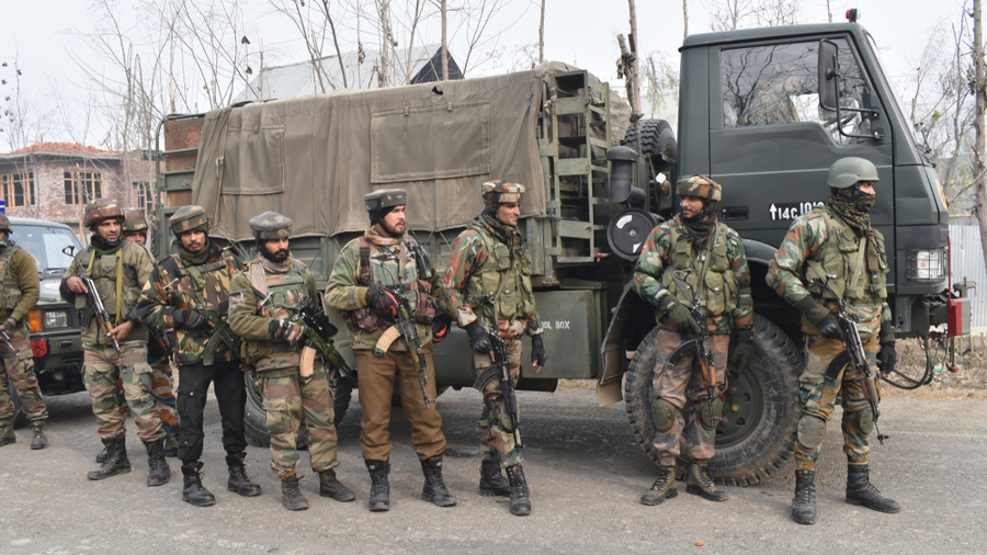Indian army troopers stand alert near a gun battle site at Mujgund, on the outskirts of Srinagar, 9 December, 2018.