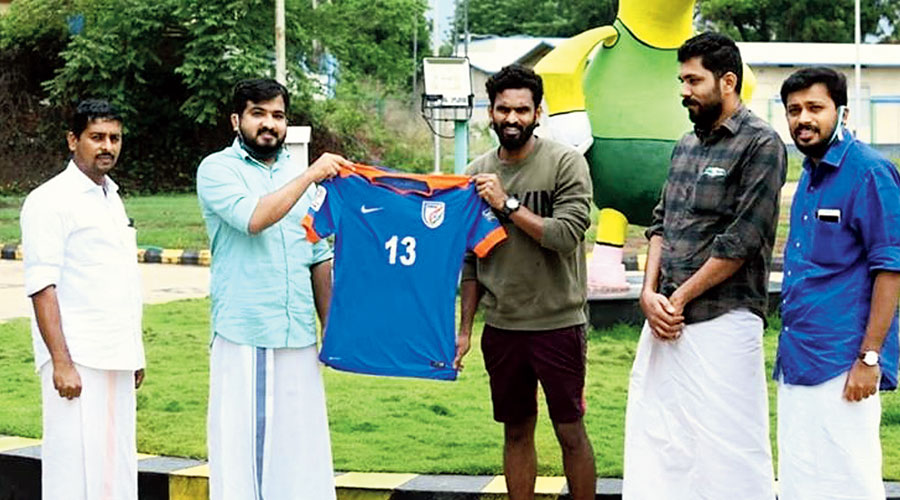 Footballer CK Vineeth (centre) donates his India jersey