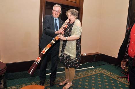 Christine Ford blows into a didgeridoo as Andrew helps her hold it. The Fords were excited to spot the wind instrument identified with the aboriginal people of northen Australia played at a party in Calcutta last January