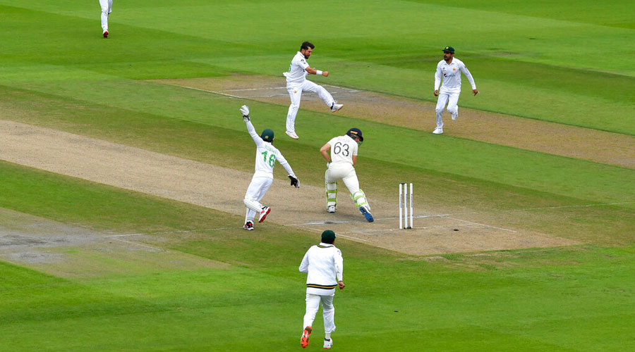 Yasir Shah jumps to celebrate the dismissal of Jos Buttler (center) during the third day of the first cricket Test match between England and Pakistan at Old Trafford in Manchester on Friday.