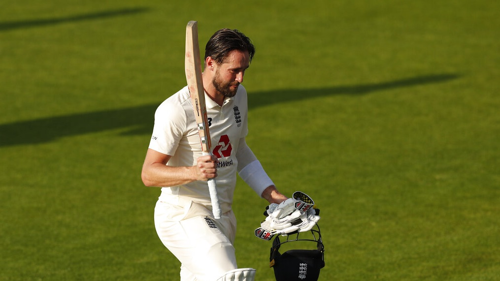 Chris Woakes raises his bat as walks off the field after their win during the fourth day of the first cricket Test match between England and Pakistan at Old Trafford in Manchester on Saturday.