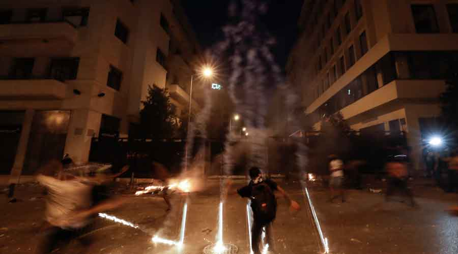 Teargas canisters fly during anti-government protest following Tuesday's massive explosion which devastated Beirut