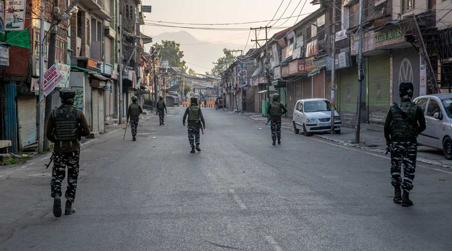 Paramilitary soldiers patrol a deserted street in Srinagar on Wednesday.