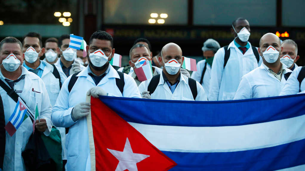 Medics and paramedics from Cuba pose upon arrival at the Malpensa airport of Milan, Italy, Sunday, March 22, 2020.