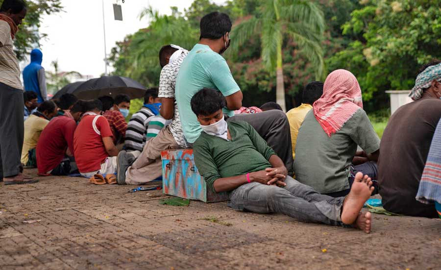 A man dozes off as migrant workers from Bengal wait to register for home bound trains in Kochi on June 3, 2020.