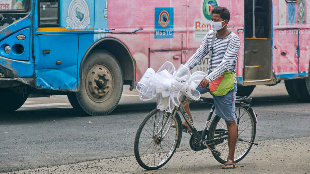 A man carrying bundles of white plastic face shields on a bicycle, Esplanade, Calcutta, August, 2020.