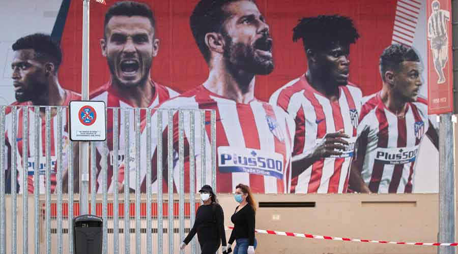 In this May 5, 2020 file photo, two women wearing face masks pass by a giant poster of Atletico Madrid soccer players at the Wanda Metropolitano stadium in Madrid, Spain.
