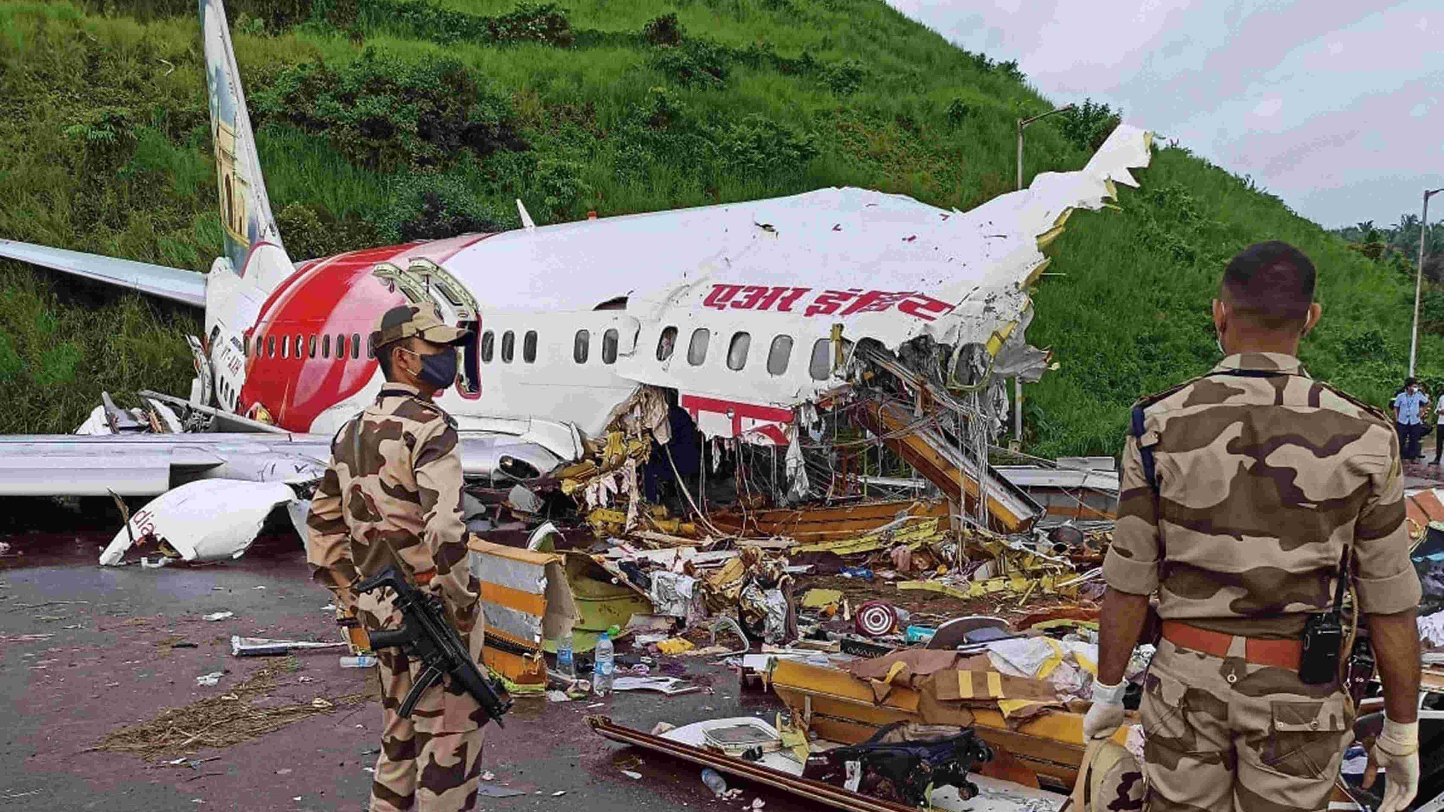 Security personnel stand guard near the mangled remains of an Air India Express flight, en route from Dubai, after it skidded off the runway while landing on Friday night, at Karippur in Kozhikode, Saturday, Aug. 8, 2020.