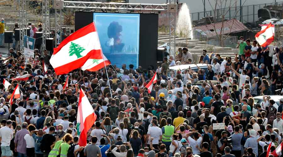 People watch on a giant screen the moment of the massive explosion, as they gather in honor of the victims at the scene of the last week's explosion, in Beirut, Lebanon, on Tuesday