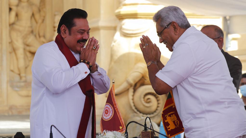 Sri Lanka's former President Mahinda Rajapaksa, left, greets his younger brother, President Gotabaya Rajapaksa, after being sworn in as the prime minister at Kelaniya Royal Buddhist temple in Colombo, Sri Lanka, Sunday, Aug. 9, 2020.