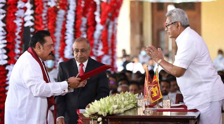 Sri Lankan President Gotabaya Rajapaksa, right, hands over credentials to his elder brother, Prime Minister Mahinda Rajapaksa
