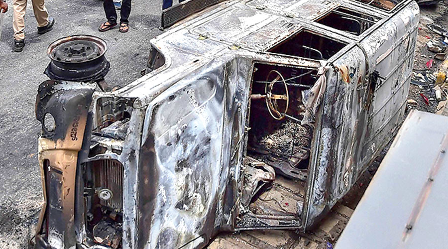 Charred remains of a vehicle vandalised by a mob over a social media post in Bangalore on Wednesday.
