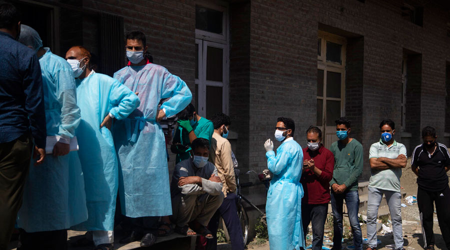Relatives and bystanders  line up to get oxygen cylinders for the patients outside a hospital in Srinagar on Wednesday.