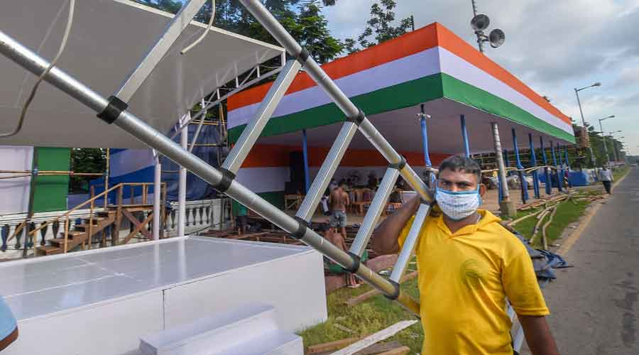 A labourer works to construct a pandal ahead of the 74th Independence Day celebrations, at Red Road in Calcutta, on Wednesday