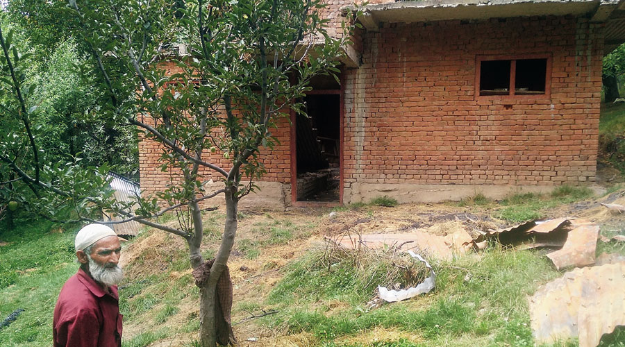 A villager stands in front of the barn in Shopian where the alleged gunfight took place