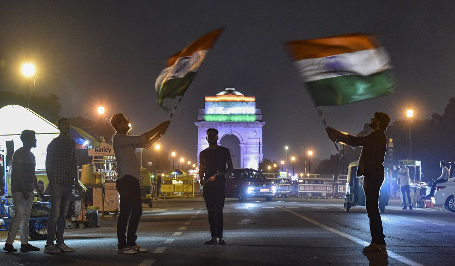 People at India Gate wave Indian national flags on the eve of Independence Day