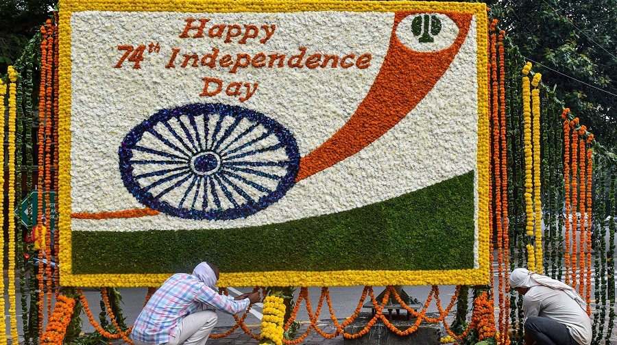 NDMC workers decorate a board with flowers to wish people on 74th Independence Day, in New Delhi.