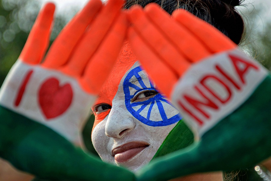 A girl with her face and hands painted in tricolour poses for a photograph, on the eve of Independence Day, in Amritsar.