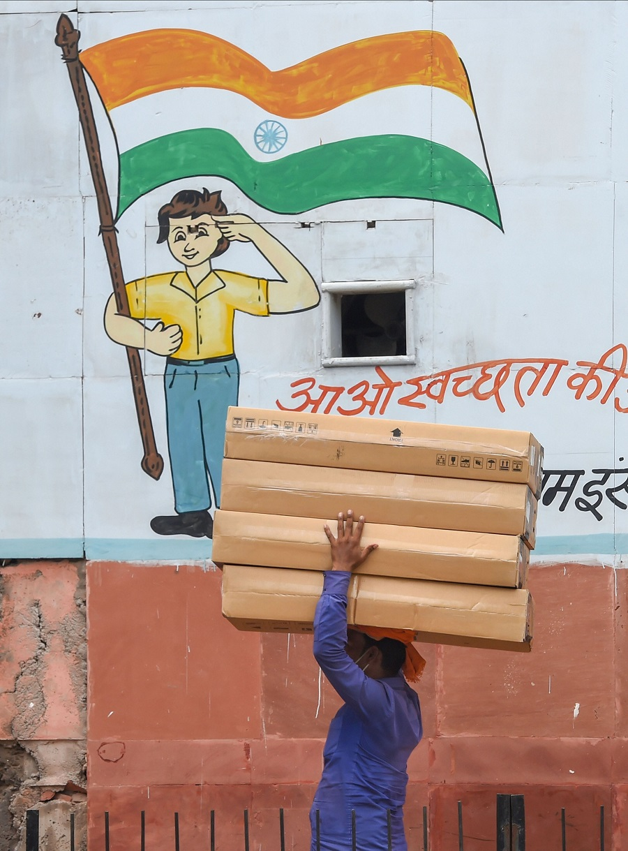 A porter walks past a wall with a Tri-colour painted on it as part of a cleanliness campaign, in New Delhi.