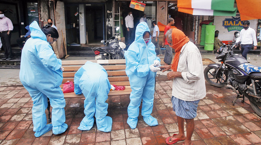 Community health workers screen a man for Covid-19 symptoms in Dharavi in Mumbai on Saturday.