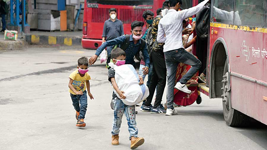 Migrants returning to Delhi run to board a bus at Anand Vihar bus terminal  on Tuesday