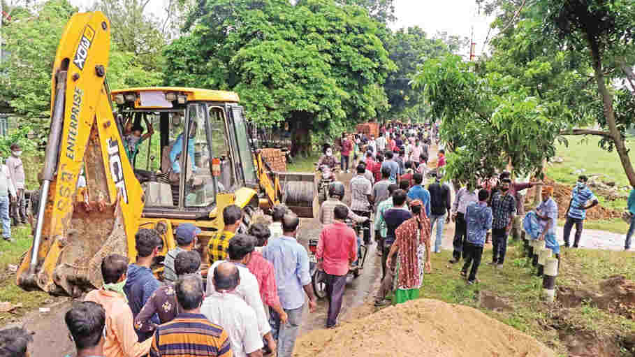 Locals gather with an earth-moving vehicle to undo the foundation work of a wall at Santiniketan Poush Mela ground, during a mass protest, in Birbhum district, Monday, Aug. 17, 2020.