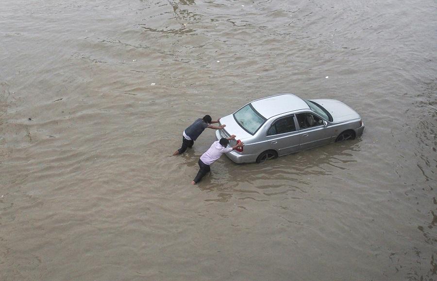 Men push a car stuck at waterlogged Hero Honda Chowk near Delhi-Gurgaon Expressway after heavy rain on Wednesday