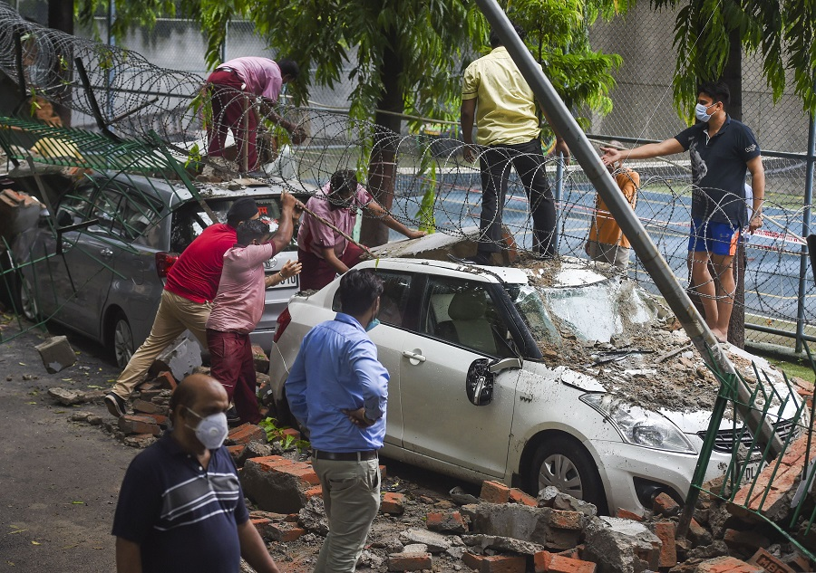 Workers remove the debris after wall of a public school collapsed due to heavy rains in New Delhi on Wednesday