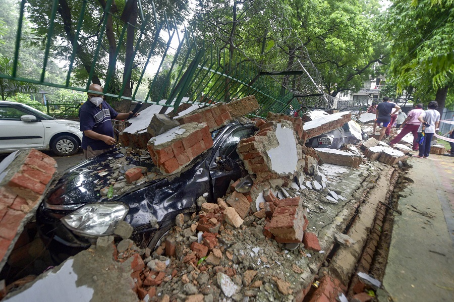 A vehicle buried under the debris after wall of a public school collapsed due to heavy rains, at Saket in New Delhi on Wednesday