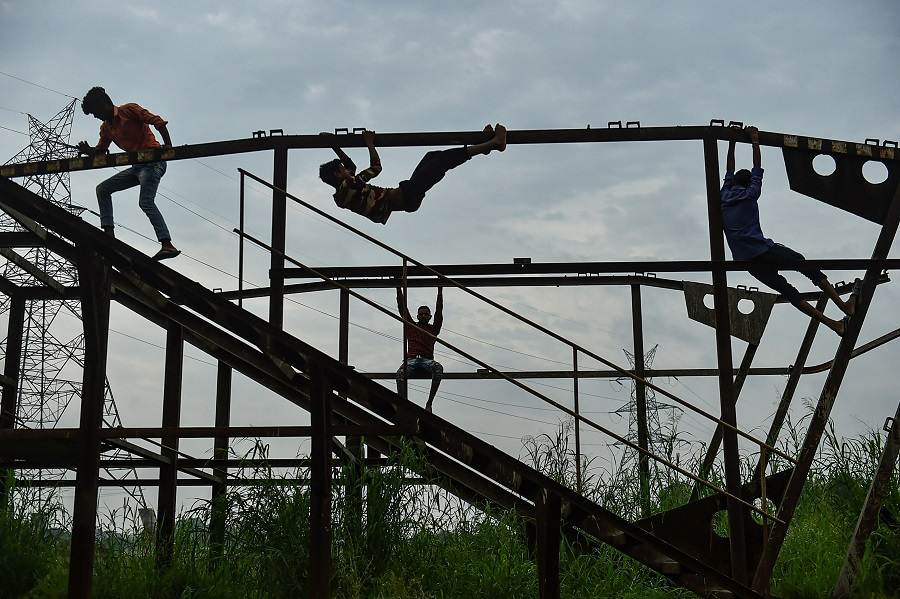 Boys play on a structure as the weather cools following heavy monsoon rain, in New Delhi on Wednesday