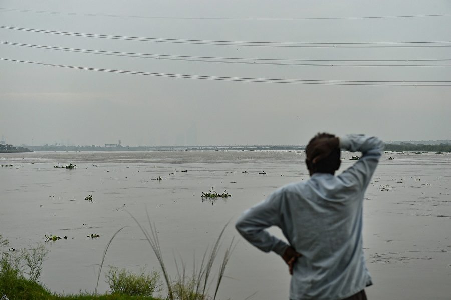 A man stands at the bank of Yamuna River as its water level rises after heavy monsoon rain in New Delhi on Wednesday