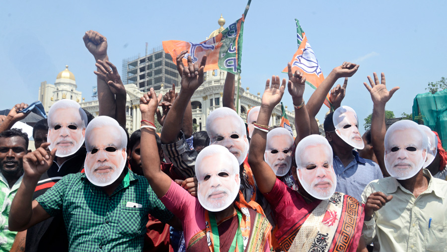BJP activists wear Narendra Modi masks and shout slogans during a campaign rally ahead of Lok Sabha elections on April 3, 2019 in Calcutta.