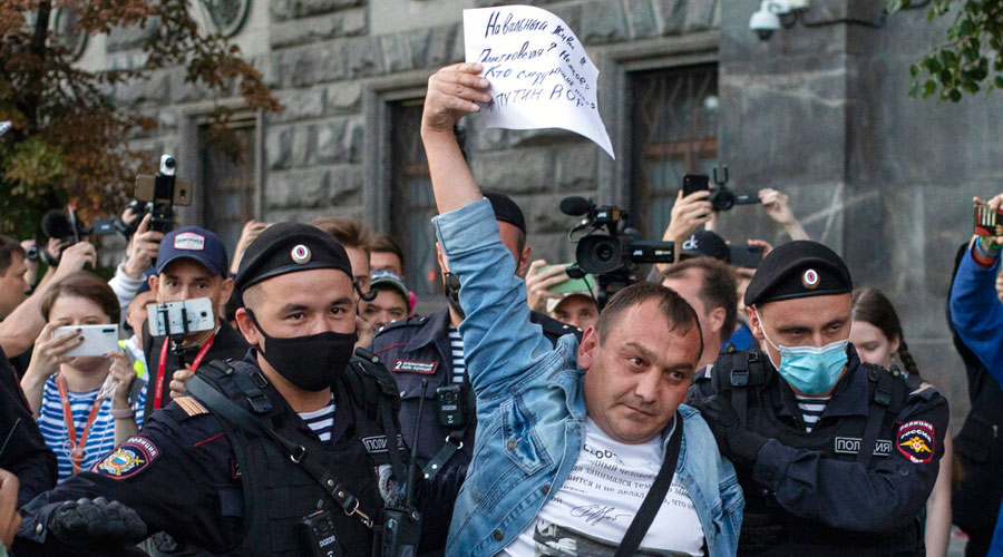 Police officers detain a protester as he comes to support Russian opposition leader Alexei Navalny in front of the building of the Federal Security Service in Moscow on Thursday.