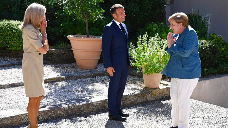 French President Emmanuel Macron, center, and his wife Brigitte Macron, left, welcome German Chancellor Angela Merkel for a meeting at the Fort de Bregancon, southern France, Thursday, Aug. 20, 2020.