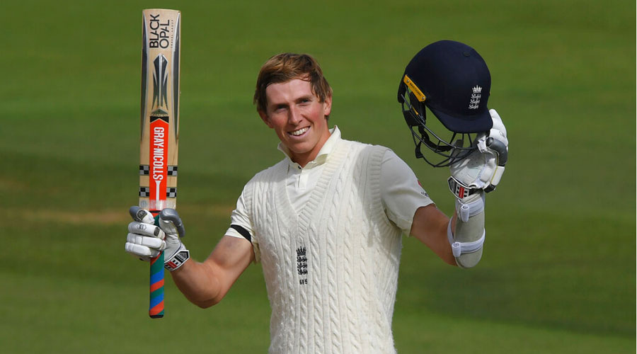 Zak Crawley raises his bat and helmet to celebrate scoring a century during the first day of the third cricket Test match between England and Pakistan in Southampton on Friday.